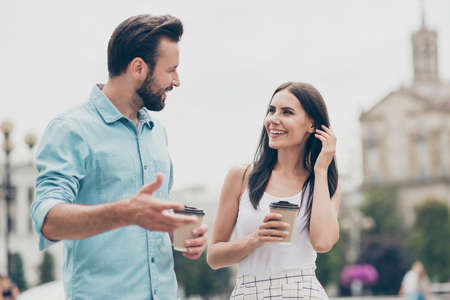 Portrait d'étudiants excités printemps les gens s'amusent promenade barbu cite à l'extérieur tenir la main tasse boisson conversation temps libre week-end robe jupe vêtements chemise bleu denim jeans rassemblement