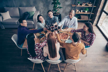Close up top above high angle photo company social crowd event hang out members buddies different race raise glasses beverage sit round table shirts formal-wear sweaters pullovers loft room indoors