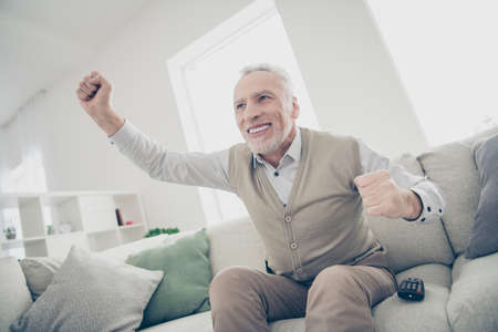 Close up photo amazing funky he him his aged man observe sports match game achievement arms hands raised air wear white shirt waistcoat pants sit comfort bright flat house living room indoors