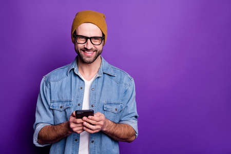Cool handsome guy holding telephone writing friends casual denim outfit isolated violet background