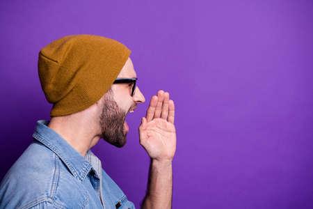Vue de côté du profil en gros plan portrait de son beau mec barbu attrayant annonçant un nouvel espace de copie de nouveauté isolé sur fond violet lilas violet brillant brillant Banque d'images