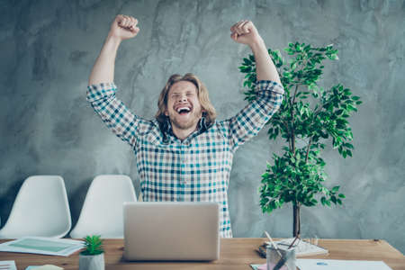 Portrait of cheerful freelancer with blonde hair screaming yeah raising fists wearing checkered plaid shirt sitting in industrial Foto de archivo