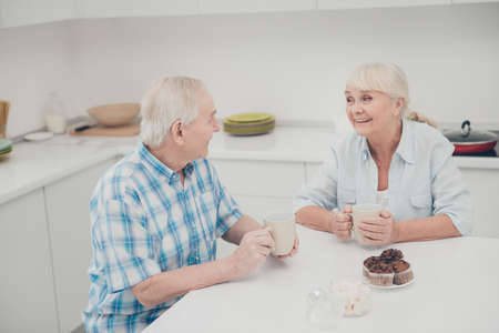 Portrait of affectionate grandparents hold hand beverage mug sit table cookies muffin biscuits look indoors