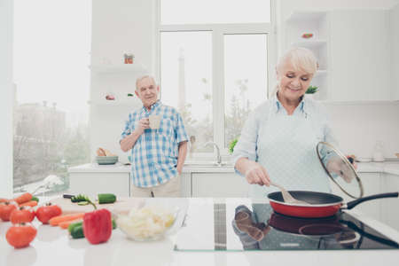 Portrait of his he her she nice attractive cheerful cheery concentrated focused careful spouses granny cooking fresh delicious domestic tasty yummy dish in modern light white interior kitchen