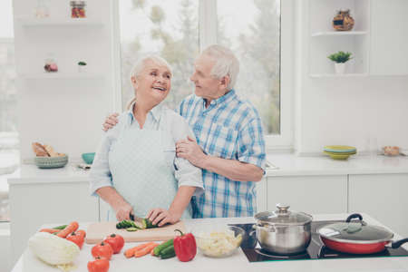 Closeup photo of two funny aged people cute pair prepare family dinner anniversary meeting wait children bright kitchen indoors