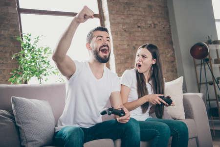 Foto von einem lustigen Paar, das drinnen auf dem Sofa sitzt und Videospiele spielt, die von unerwartetem Gewinnen und Verlieren begeistert sind?