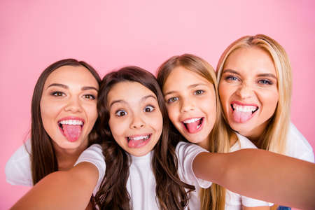 Self-portrait of four nice attractive lovely charming comic playful cheerful cheery long hsired girls having fun spending free time fooling maternity isolated on pink pastel background