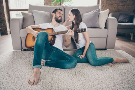 Two nice attractive lovely tender cheerful cheery positive people having fun spending day holiday weekend sitting on floor playing songs melody at home house apartment indoors Stockfoto