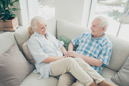Above high angle view of her she his he two nice attractive lovely cheerful cheery people soulmates sitting on cosy divan spending time in light white interior living-room house