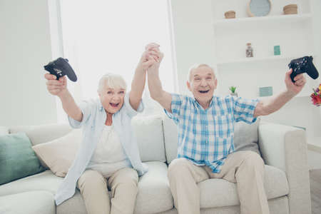Portrait of her she his he two nice attractive cheerful cheery glad excited ecstatic positive spouses having fun enjoying battle contest win winner in light white interior living-room indoors