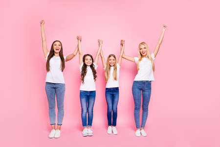 Full body photo of two small and two students ladies raising arms up wear casual outfit isolated pink background