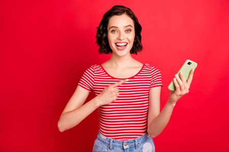 Portrait of her she nice attractive lovely cheerful cheery glad positive wavy-haired girl showing app 5g fast speed connection isolated over bright vivid shine red background