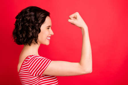 Side photo of gorgeous attractive charming wavy curly girl having just returned home from gym bragging about her muscles while isolated with red background