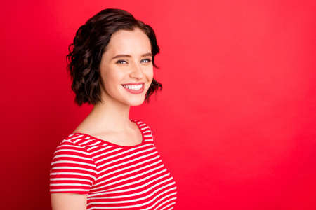 Photo of wonderful wavy curly woman of elation standing in half profile and happily smiling at camera while isolated with red background 免版税图像