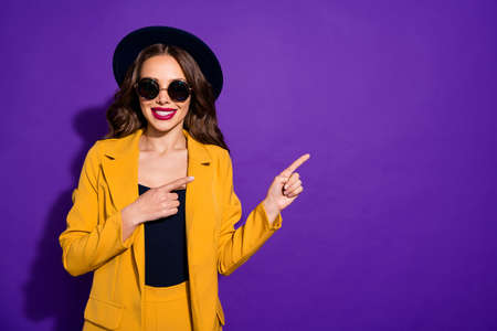 Portrait of her she nice-looking lovely charming cute cheerful cheery wavy-haired lady pointing two forefingers aside ad isolated over bright vivid shine violet lilac purple background