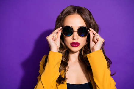 Photo of cool astonishing girl watching into camera through sunglass while being isolated with purple background