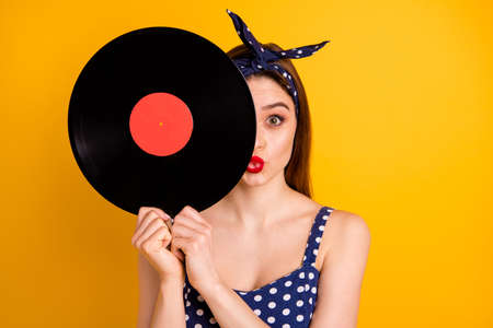 Close-up portrait of her she nice attractive lovable girlish funny straight-haired lady holding in hands hiding behind round disc sending you kiss isolated on bright vivid shine yellow background Stock fotó