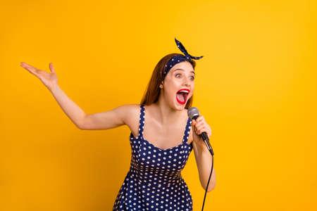 Portrait von ihr, sie schöne attraktive mädchenhaft fröhliche fröhliche, fröhliche, glatte Dame, die in den Händen hält, Mikrofon singt neue coole populäre Tracks einzeln auf hell leuchtendem, gelbem Hintergrund