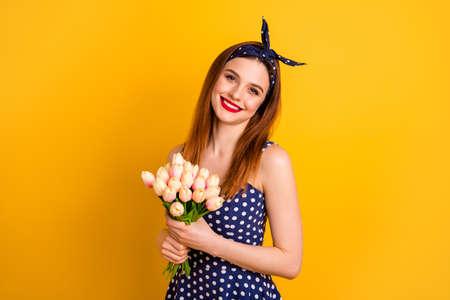 Porträt von ihr, sie sieht gut aus, attraktiv, hübsch, glamourös, fröhlich, fröhlich, gerade, Floristin, die in den Händen hält Blumenbündel einzeln auf hell leuchtendem, gelbem Hintergrund Standard-Bild