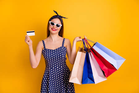 Portrait of nice lady hold hand bags bright boutique wear trendy headband red lips-stick eyewear eyeglasses isolated over yellow background