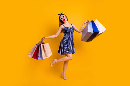 Full length photo of lovely youth hold hand bags have rest black friday wear head band eyewear eyeglasses isolated over yellow background