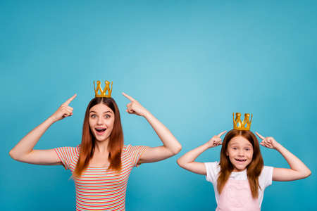 Excited foxy little lady and mommy indicating fingers headwear dressed in casual outfit isolated blue background
