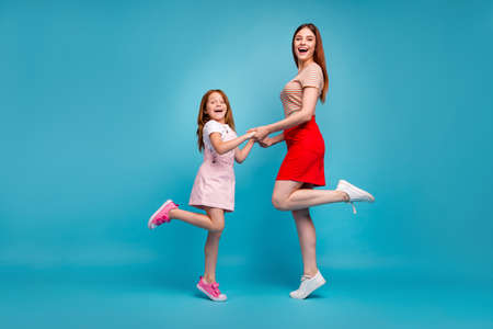 Photo of foxy little lady and her mom holding hands wear casual clothes isolated blue background