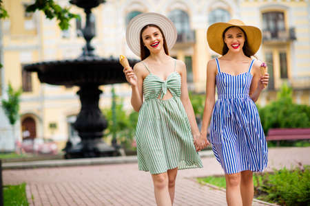 Portrait of joyful people with brunnete hair red lipstick smiling moving in city Фото со стока