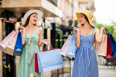 Portrait of cute ladies having lipstick and many bags looking with toothy smile in city Фото со стока
