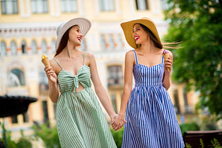 Portrait of lovely ladies with brunette hair red lipstick holding hands moving in city center