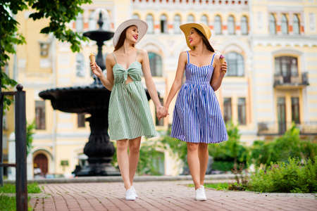 Full length photo of charming ladies with brunette hairstyle red lipstick holding hands moving in town Фото со стока