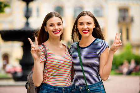 Close up photo of sweet people with red brunette hair making v-signs wearing striped t-shirt denim jeans rucksack in city outdoors