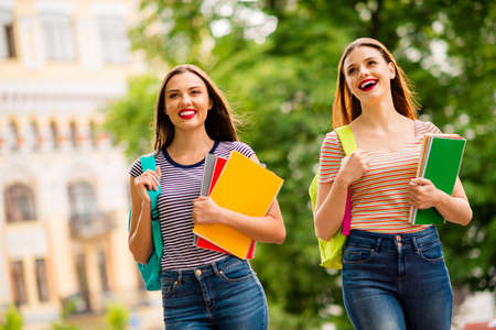 Portrait of cheerful ladies with red lipstick holding note books wearing striped t-shirt denim jeans in town outdoors