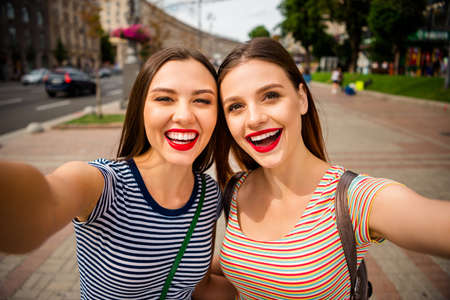 Close up photo of cheerful ladies with red lipstick making photos wearing striped t-shirt in town