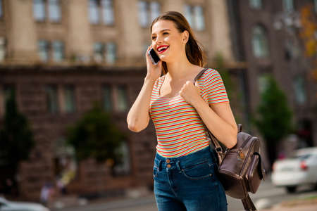 Profile side photo of cheerful lady with foxy ginger red lipstick hairstyle calling speaking wearing rucksack striped t-shirt denim jeans in city