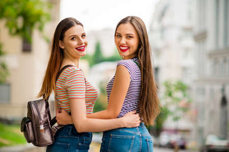 Back side photo of charming youth hugging with tooth smile wearing striped t-shirt denim jeans in city outdoors