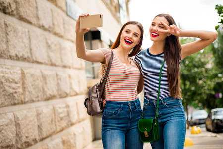 Portrait of lovely buddies with brunette red hair redhair pomade making photos v-sign wearing striped t-shirt denim jeans in town Stock fotó