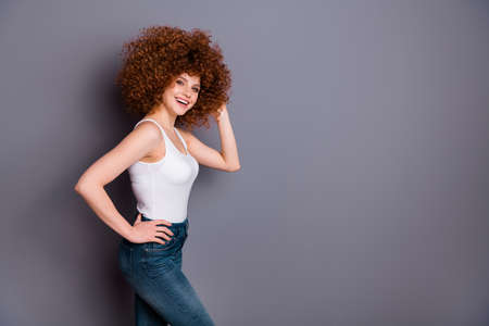 Profile photo of curly hairstyle lady toothy beaming smile playful mood wear white tank-top jeans denim isolated grey background