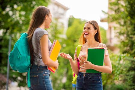 Back side portrait of pretty fellows with red brunette hair lipstick hold notebooks rucksack wear striped t-shirt denim jeans in city center Фото со стока