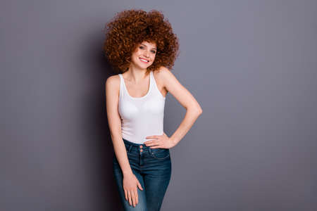 Photo of curly hairstyle lady toothy beaming smile playful mood wear white tank-top jeans denim isolated grey background