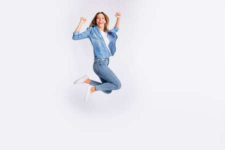 Full length body size photo of shouting nice glad having fun funky funny cool emotional lady raising fists up isolated grey background Standard-Bild