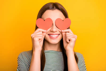 Photo of shy girl hiding her eyes behind paper reddish hearts while isolated with yellow background