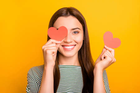 Photo of cute playful girl looking out of one hearts given her as present for valentine day while isolated with yellow background