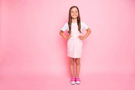 Ganzkörperfoto der kleinen Dame mit braunem Haar Urlaub Freizeit Hände Seiten tragen rosa Sonnenkleid T-Shirt isoliert rosa Hintergrund