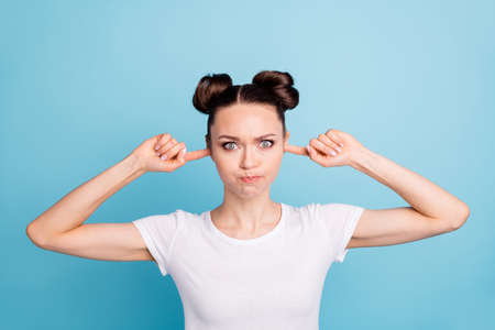 Pretty lady index fingers inside ears holding breath moody wear white casual t-shirt isolated blue background Imagens