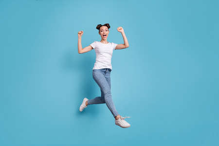 Full body photo of jumping lady came fihish race first wear white casual t-shirt jeans denim isolated blue background Standard-Bild