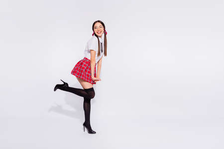 Full length body size profile side view of her she nice attractive slim fit thin lovely cheerful cheery girl wearing checkered skirt shadow having fun isolated on gray light white background