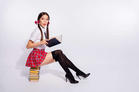 Full length side profile body size photo beautiful she her teacher sit reader book pile interested curious story end finish tails wear short red checkered costume pantyhose isolated white background Foto de archivo
