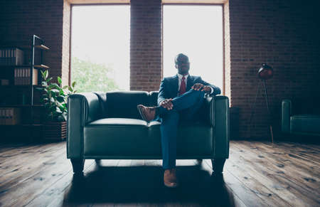 Photo of dark skin macho guy sitting office sofa wear specs and corporate costume