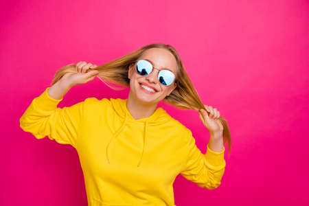 Photo of crazy lady playing with curls wear yellow hoodie pullover isolated pink background